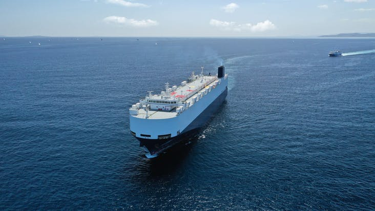 Aerial drone photo of huge car carrier ship RO-RO_shutterstock_1822736288
