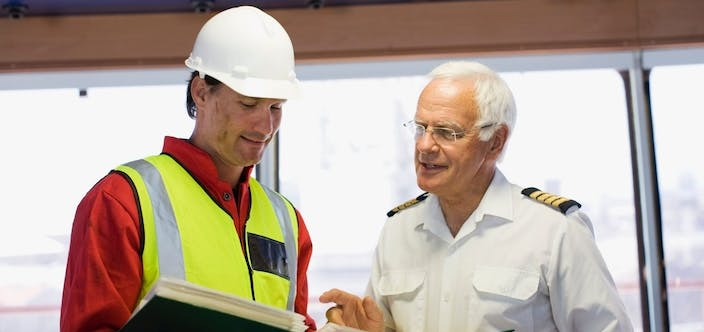Captain of a ship discussing with a worker_shutterstock_1013460640