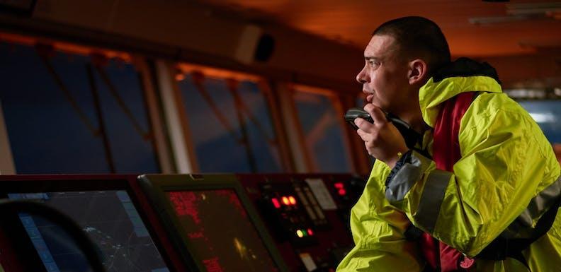 ship crew performing daily duties with VHF radio, binoculars, logbook, standing nearby to ECDIS shutterstock_1471641632
