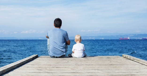 Father with son sitting on the sea pier